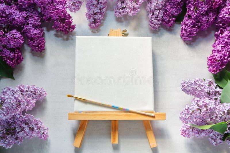 Leeg canvas op schildersezel, borstel voor het schilderen en lilac bloemen royalty-vrije stock afbeeldingen