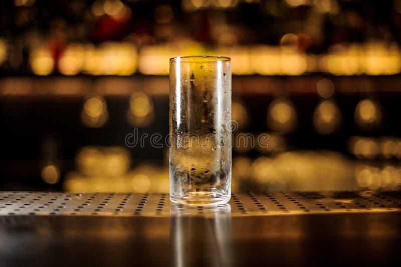Leeg cilindrisch cocktailglas die zich op de barteller bevinden stock afbeelding