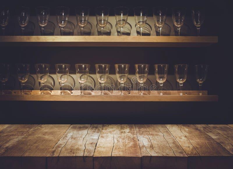 Leeg de bovenkant van houten lijst met vaag tegenbar en het drinken glas stock foto