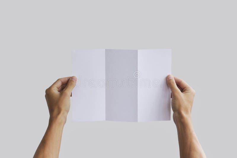 Leeg de brochureboekje van de handholding in de hand Pamfletpresentatie De mens van de pamflethand De mens toont compensatiedocum royalty-vrije stock afbeeldingen