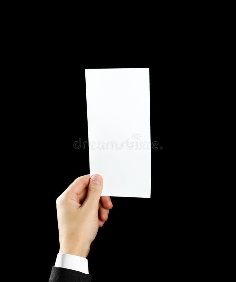 Leeg de brochureboekje van de handholding in de hand Geïsoleerde op zwarte achtergrond De mens toont compensatiedocument Bladmalp royalty-vrije stock foto