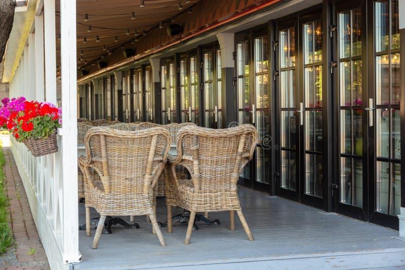 Leeg de zomerterras van een comfortabel restaurant met rieten meubilair en bloemen royalty-vrije stock foto