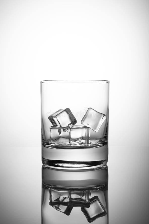Leeg die rotsenglas met ijsblokjes, op witte achtergrond worden geïsoleerd stock foto's