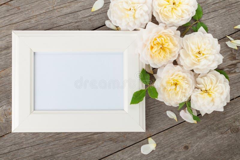 Leeg fotokader en witte rozen stock foto's