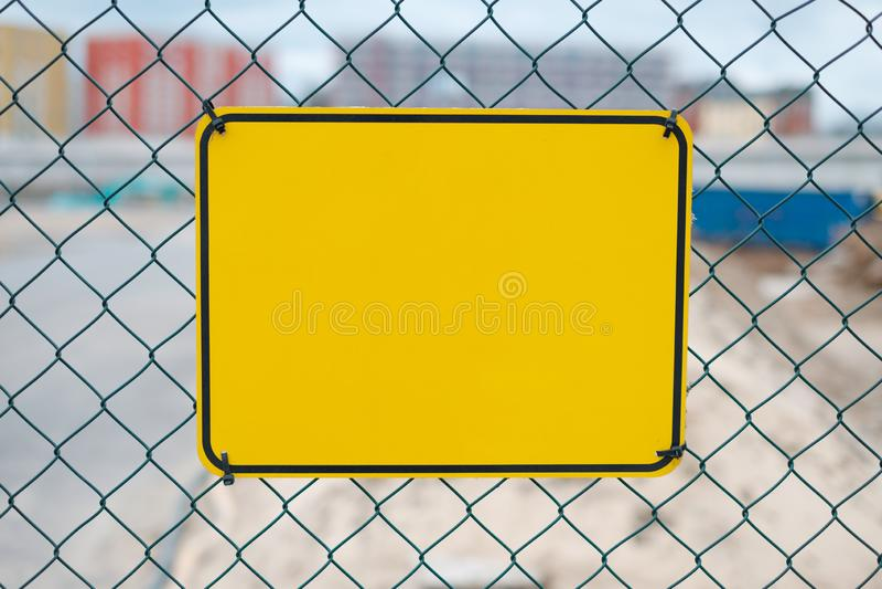 Leeg geel teken op bouwwerfomheining - waarschuwingsbordmodel stock foto's