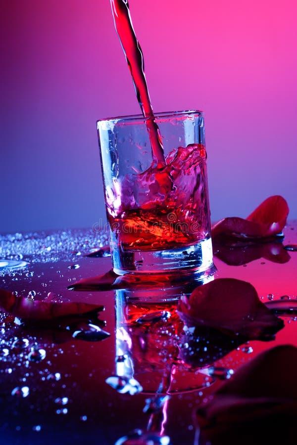 Leeg glas met roze bloemblaadjes stock afbeelding