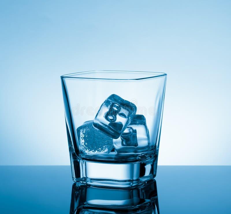 Leeg glas whisky op zwarte lijst met bezinning en ijs op lichtblauwe tintachtergrond stock afbeelding