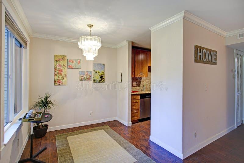 Leeg het dineren gebied met lichte muren en hardhoutvloer stock foto's