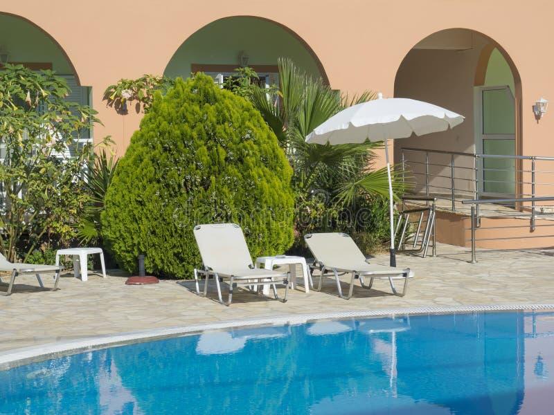 Leeg hotel zwembad tijdens zonnige dag, de zomervakantie Mening van blauw water in pool, witte sunbeds, paraplu en stock foto