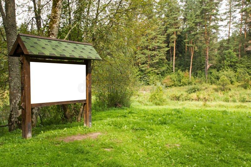 Leeg houten aanplakbord in het bos stock foto's