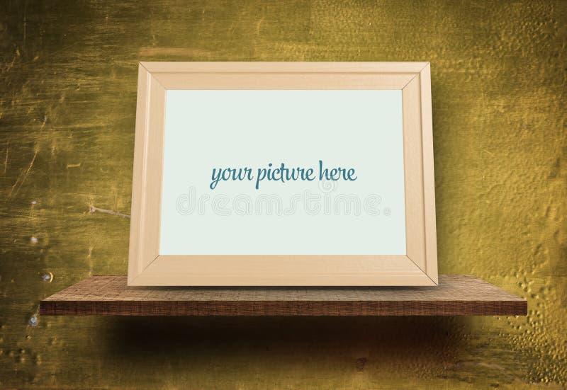 Leeg houten fotokader op gouden muur stock foto