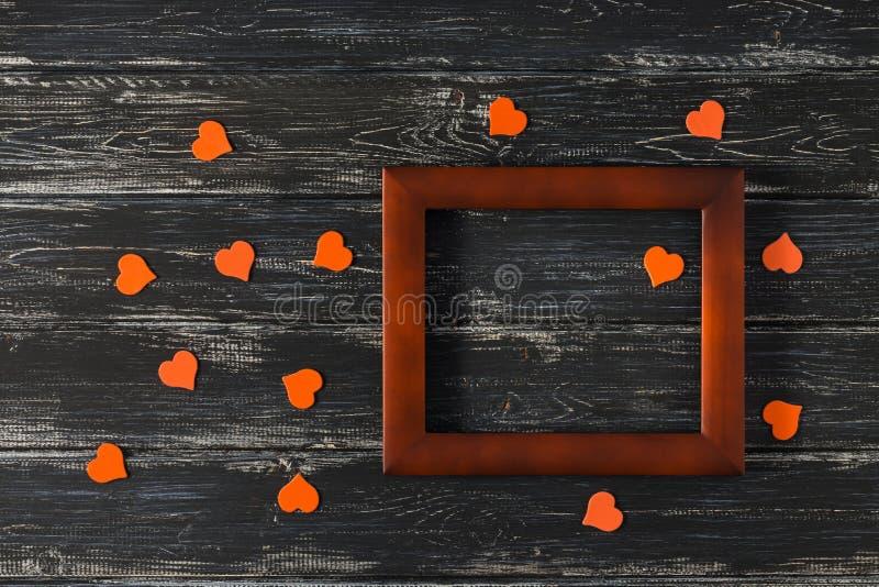 Leeg houten kader met harten op een geweven achtergrond Oranje harten Lege plaats royalty-vrije stock foto