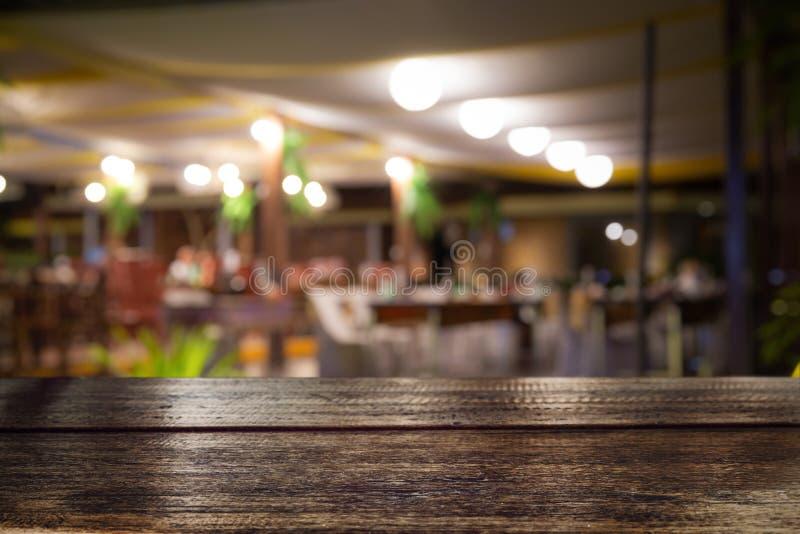 Leeg houten lijstbovenkant en onduidelijk beeld van geconcentreerde nachtbar of restaurantachtergrond/selectief royalty-vrije stock afbeelding