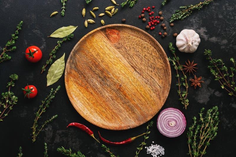 Leeg houten plaat en kader van kruiden, kruiden en groenten op een donkere steenachtergrond De hoogste vlakke mening, legt royalty-vrije stock fotografie