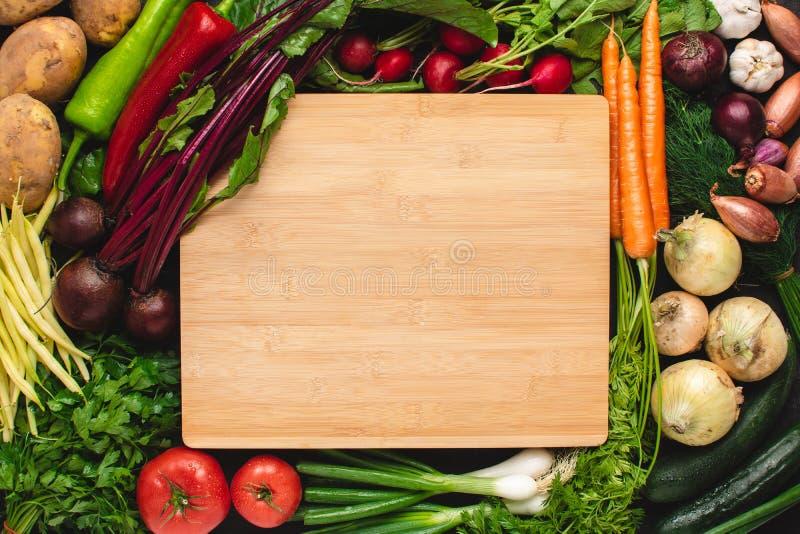 Leeg Houten Scherp Raadsmodel met Verse Groenten Vegetarisch ruw voedsel royalty-vrije stock fotografie