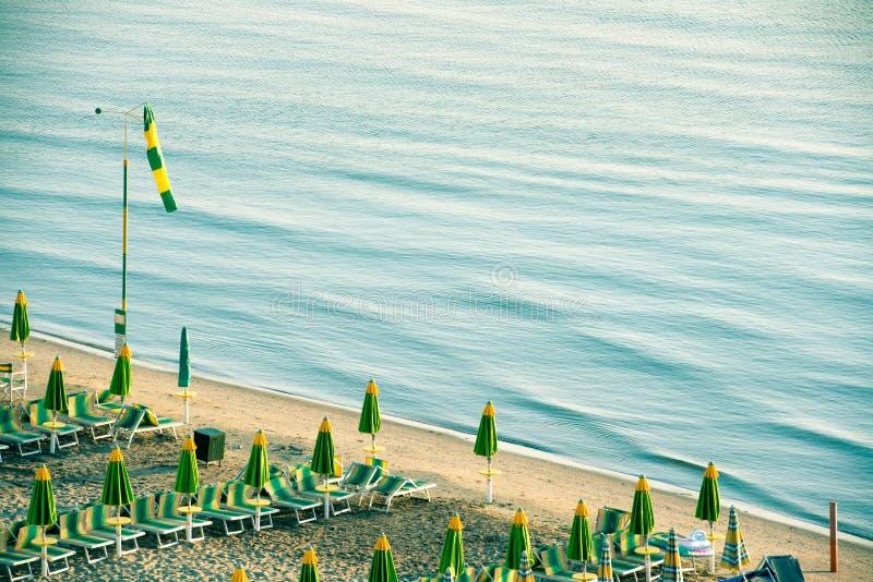 Leeg Italiaans strand met paraplu's in vroege ochtend royalty-vrije stock foto