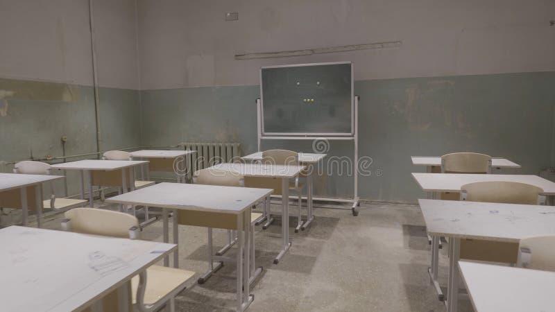 Leeg klaslokaal met houten bureaus, witte en groene schoolborden in school Leeg Klaslokaal Verlaten Schoolklaslokaal stock afbeelding