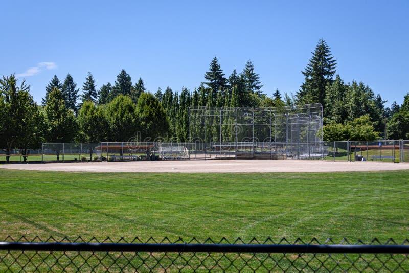 Leeg lokaal honkbalveld op een zonnige dag, mening van over achteromheining van honkbaldiamant en dugouts, met hout en blauwe hem royalty-vrije stock foto