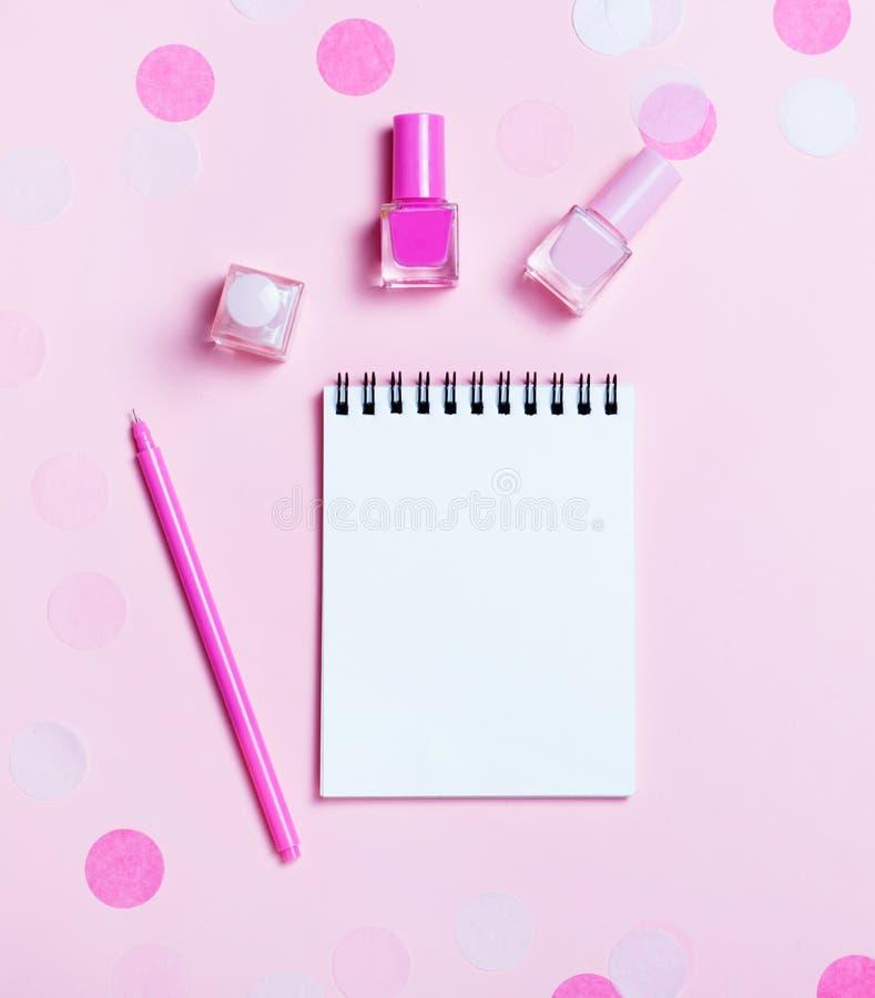 Leeg notastootkussen en kleurrijke nagellakken op roze confettienachtergrond royalty-vrije stock foto