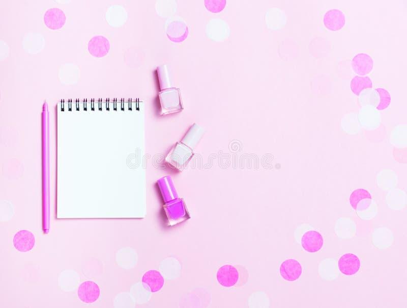 Leeg notastootkussen en kleurrijke nagellakken op roze confettienachtergrond stock fotografie