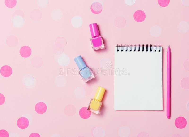 Leeg notastootkussen en kleurrijke nagellakken op roze confettienachtergrond royalty-vrije stock foto's