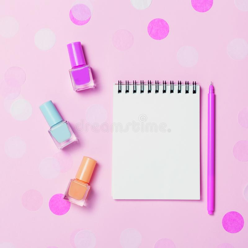 Leeg notastootkussen en kleurrijke nagellakken op roze confettienachtergrond stock foto