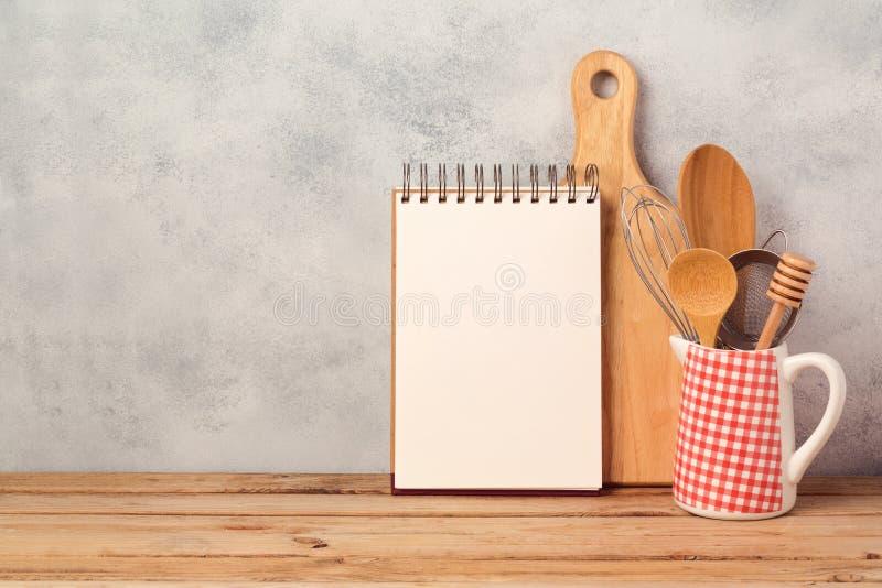 Leeg notitieboekje en keukengerei op houten lijst over rustieke achtergrond stock afbeelding
