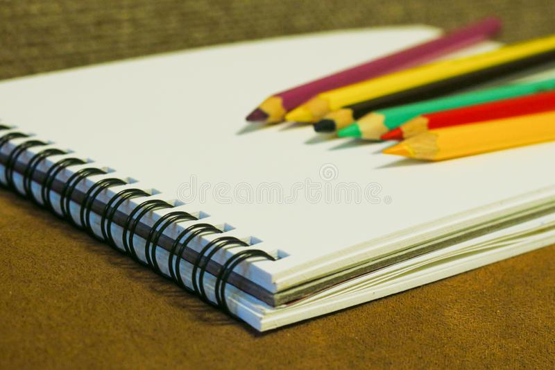 Leeg notitieboekje en kleurrijke potloden op bruine achtergrond stock afbeelding