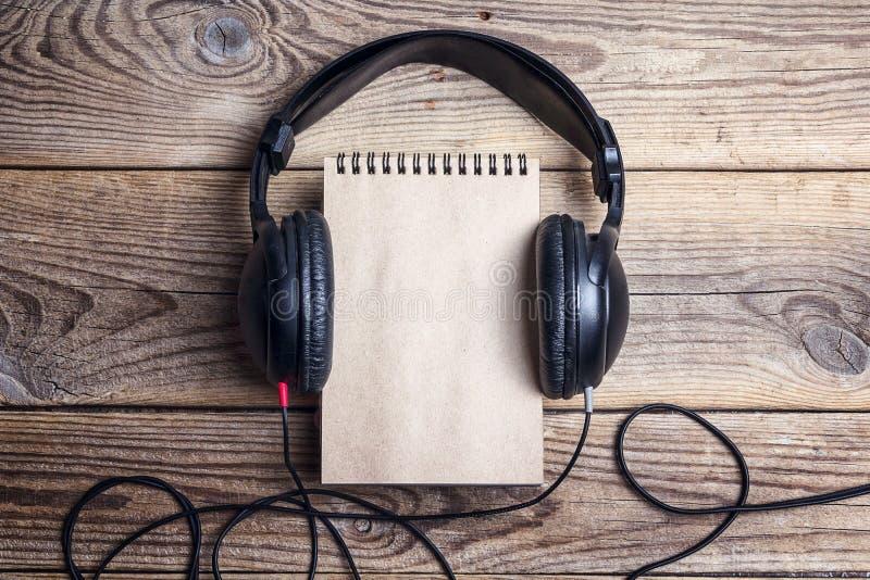 Leeg notitieboekje met hoofdtelefoons op het op houten achtergrond royalty-vrije stock afbeelding