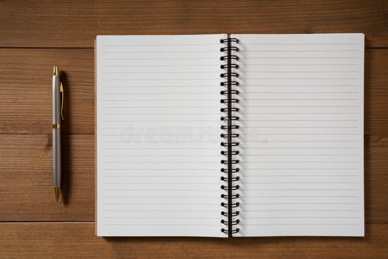 Leeg notitieboekje met pen op bruine houten lijst royalty-vrije stock afbeeldingen