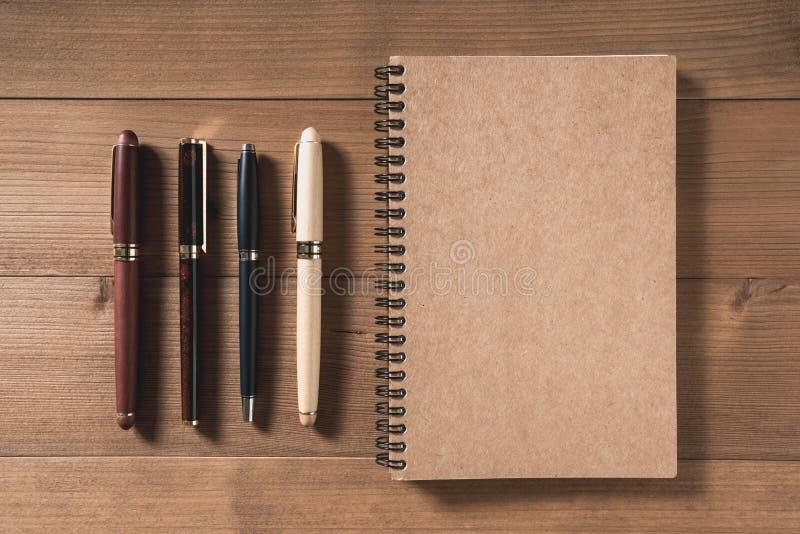 Leeg notitieboekje met pen op bruine houten lijst stock foto