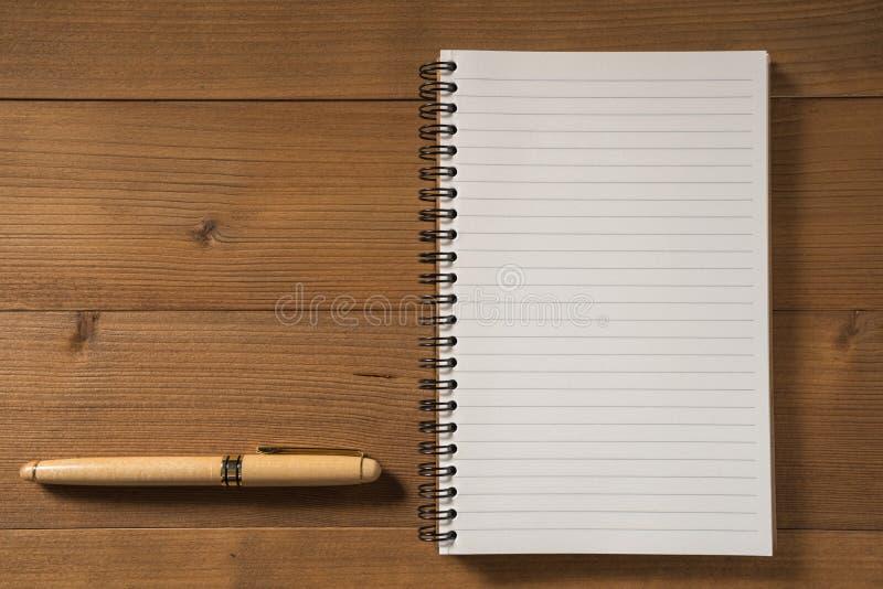 Leeg notitieboekje met pen op bruine houten lijst royalty-vrije stock fotografie