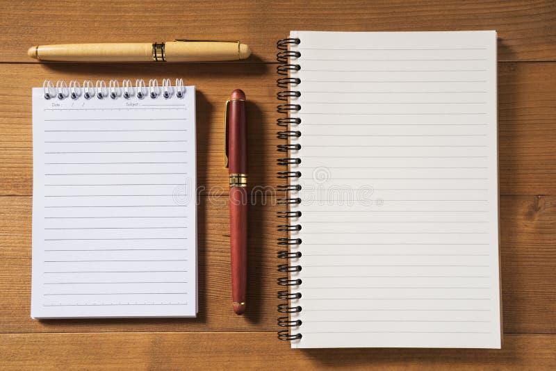 Leeg notitieboekje met pen op bruine houten lijst stock foto's