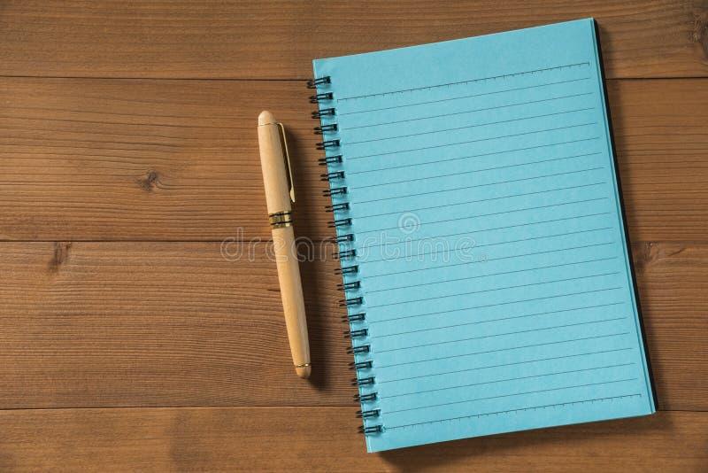 Leeg notitieboekje met pen op bruine houten lijst royalty-vrije stock foto