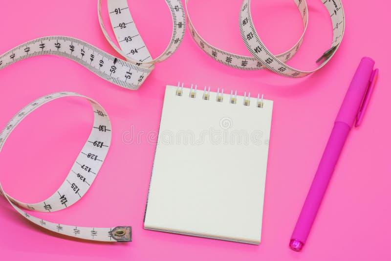 Leeg open notitieboekje met centimeterband op roze achtergrond met ruimte voor concept van het tekst of het bedrijfsvoedsel stock foto's
