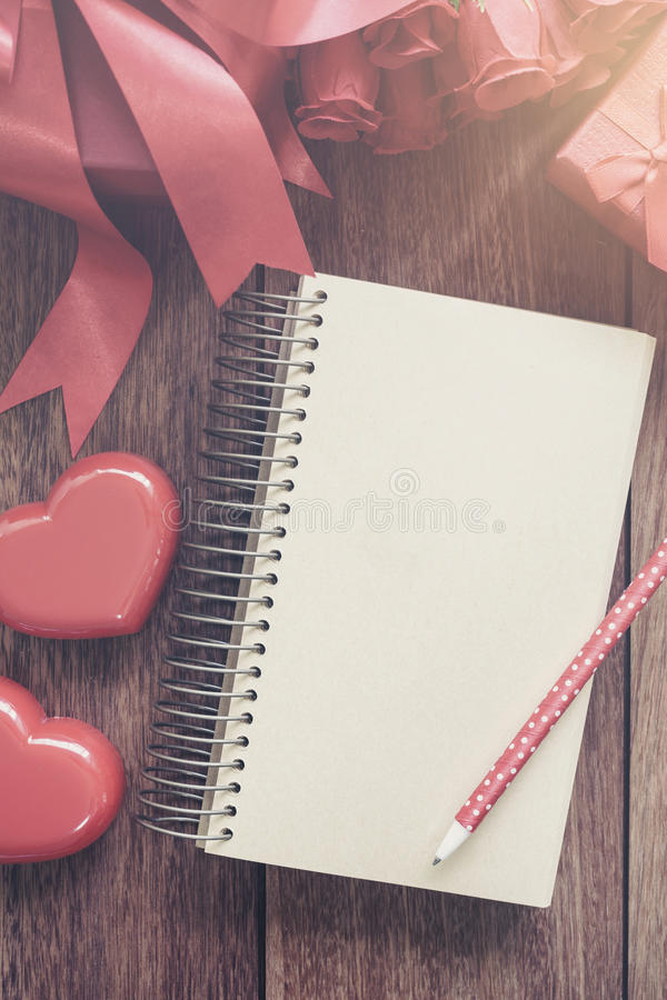 Leeg open notitieboekje met giftdoos en rode hartvorm stock foto