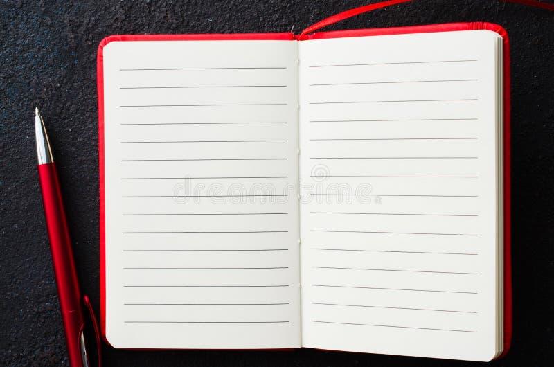 Leeg open rood notitieboekje met rode pen op donkere achtergrond Leeg document voor tekst royalty-vrije stock afbeelding