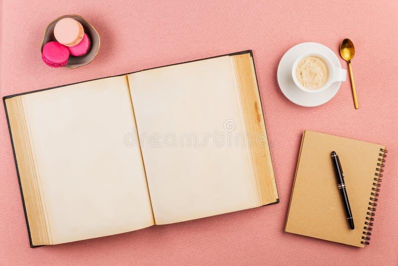 Leeg oud boek open met roze Franse macarons op de kant, de koffiekop, de gouden lepel, het notitieboekje en de pen over een roze  royalty-vrije stock afbeeldingen