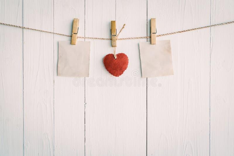 Leeg oud document twee en het rode hart hangen Op witte houten stock fotografie