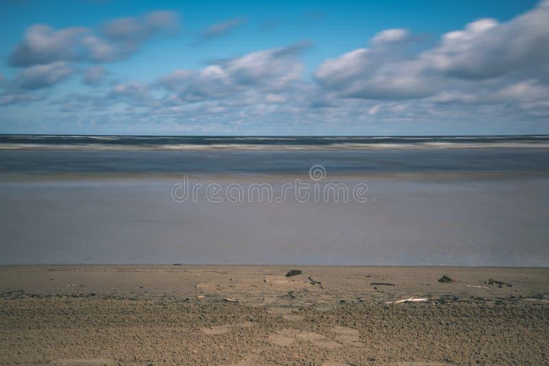leeg overzees strand in de lente met sommige vogels en vrachtschepen op royalty-vrije stock foto's