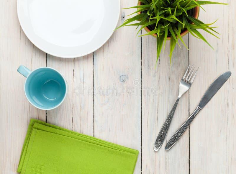 Leeg plaat, kop en tafelzilver over witte houten lijstbackgrou royalty-vrije stock afbeeldingen