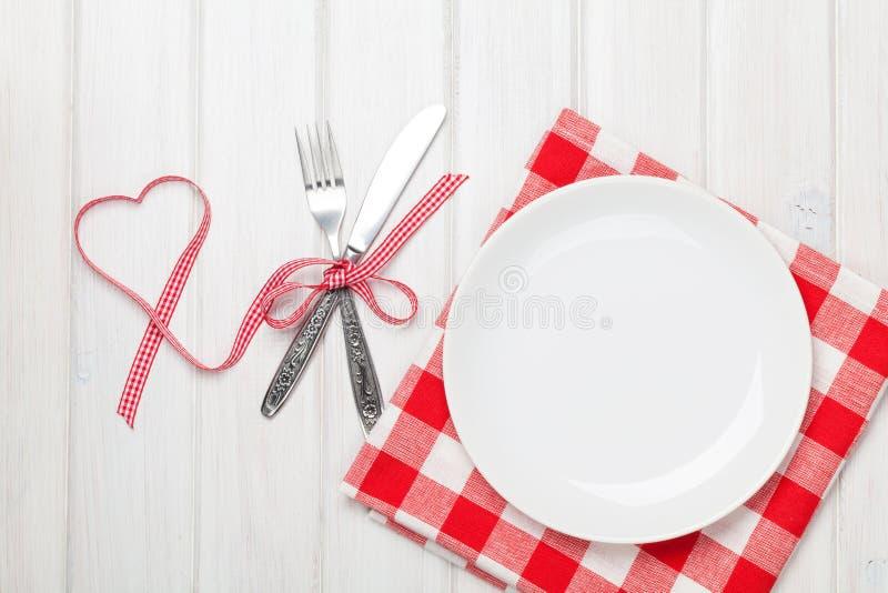 Leeg plaat, tafelzilver en van de valentijnskaartendag hart gevormd lint stock foto's