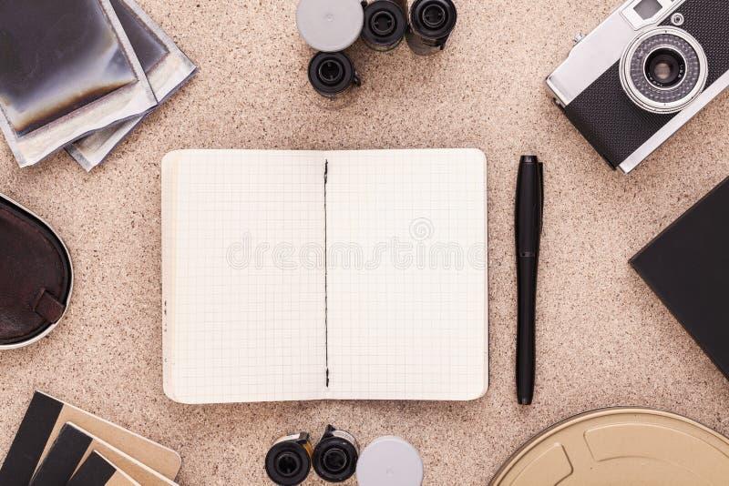 Leeg plakboek met camera en broodje van films op cork houten bureau Vlak leg Mening van hierboven stock afbeeldingen