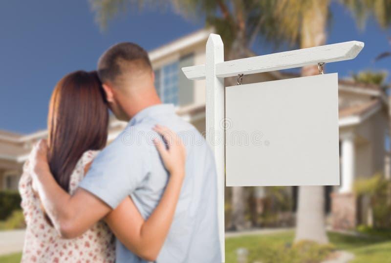 Leeg Real Estate-Teken en Militair Paar die Huis bekijken royalty-vrije stock foto