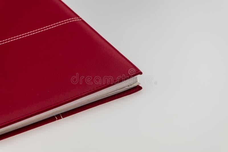 Leeg rood hardcoverboek op witte achtergrond met exemplaar stock afbeeldingen