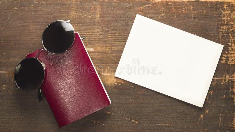 Leeg rood paspoort en ronde zonnebril met een lege prentbriefkaar op een houten achtergrond stock afbeelding