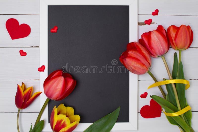 Leeg schoon zwart bord met rode tulpen en harten Hoogste mening royalty-vrije stock afbeeldingen