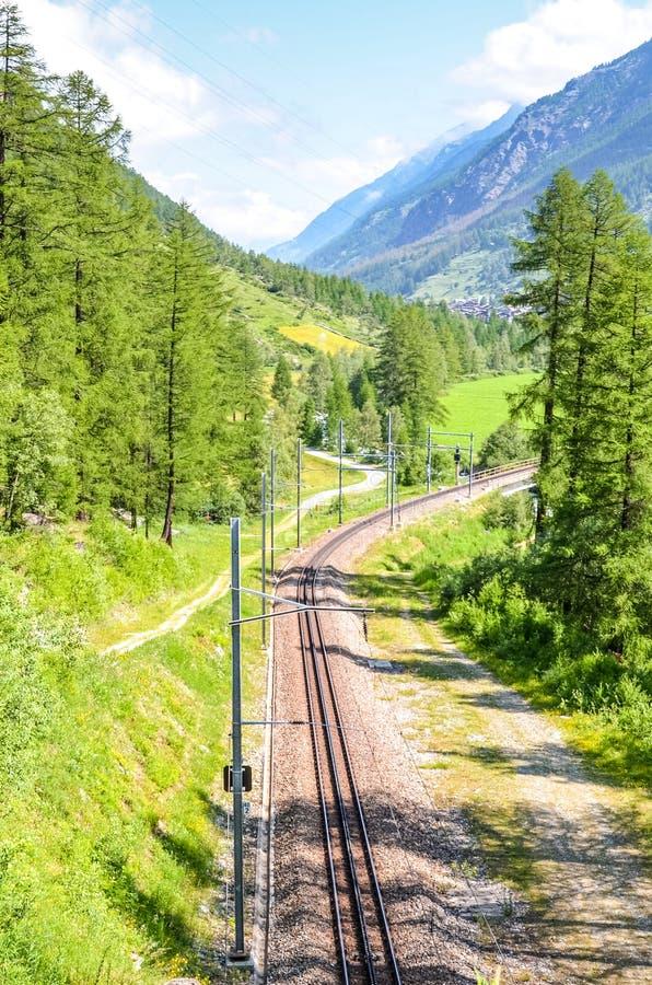 Leeg spoorwegspoor dat door groen bos wordt omringd dat op een zonnige dag wordt gefotografeerd Bergen op achtergrond Spoorweg, s stock fotografie