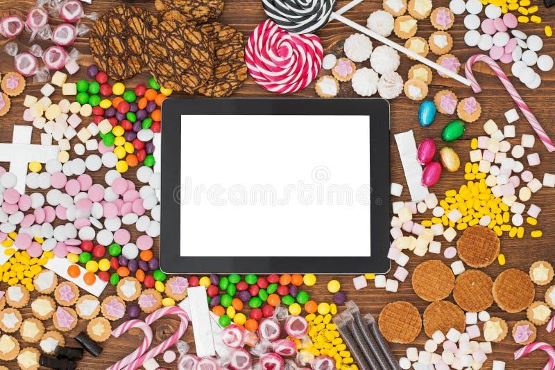 Leeg tabletcomputer en suikergoed stock afbeelding