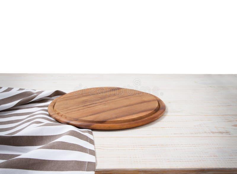 Leeg tafelkleed op houten lijst en pizza scherpe raad die op witte achtergrond wordt geïsoleerd Selectieve nadruk plaats voor voe stock afbeelding